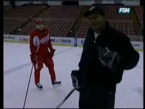 Professional hockey player plays keep away with reporter. The hand-eye cooridination is non-human