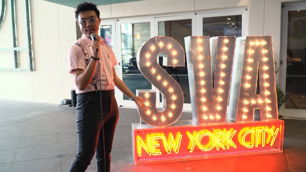 A man with glasses singing next to a lighted SVA New York City sign.