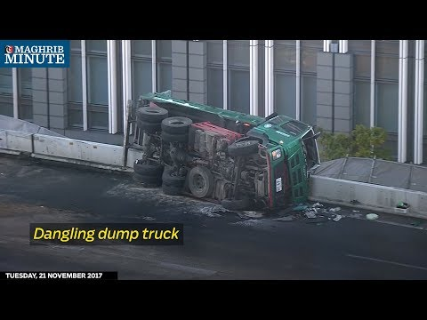 A dump truck was left dangling over the edge of a highway in downtown Tokyo on Tuesday