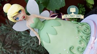 How to make a TinkerBell cake as a Disney Princess doll cake.I get a lot of Disney princess doll cake requests here on YouTube and Tinkerbell was the next one on my list, what other characters do you want to see in the future? :)I use a polystyrene ball inside the head to make it lighter which is okay as long as it is not in contact with any of the cake or any other parts you wish to eat. Alternatively you can use modelling paste for the full head, but you will need to make sure it is well supported.CAKE MASTERS NOMINATION AWARDS - If you enjoy watching Zoe's Fancy Cakes tutorials and would like to nominate us for the Cake Masters Awards 2017 for the 'Best Learning Experience Award' You can do so here - http://www.surveygizmo.com/s3/3678052/2017-CakeMastersAwards-Nominations-Form(Feel free to nominate me for any other categories you think I deserve too!) It will also ask you for a link to my website - www.zoesfancycakes.co.uk/or a link to my Facebook page - https://www.facebook.com/zoesfancycakes/Thanks so much in advance everyone! :) Nominations close 31st August 2017Tools and products used in this video - Fondant / roll out icing - http://amzn.to/1TCs62ZCake modelling tool - https://www.facebook.com/commerce/products/1878762348816211/Craft mat - http://amzn.to/2dMKpl9Edible pearls - http://amzn.to/2tVxs1ZLarge round cutter -Cake dowel - http://amzn.to/2dbTuSBSkin tone sugarflair - http://amzn.to/1TQs585Royal blue sugarflair - http://amzn.to/2sQ14ZMExtra black sugarflair - http://amzn.to/2st0mSFDark brown sugarflair - http://amzn.to/2tPrmQ2Daffodil yellow sugarflair - http://amzn.to/2sPrw5Rballing tools - http://amzn.to/1ZQfKTzcircle plunger cutters - http://amzn.to/1OdVB3iPalette petal dust colours - http://tinyurl.com/ngup2v7Basic Victoria sponge cake recipe - Ingredients: 225g butter225g caster sugar4 eggs225g self-raising flour 1 tsp vanilla essenceMethod:Cream together the butter and sugar, then beat in the eggs and vanilla essence. Once smooth and creamy, fold in the flour.Pour in to a greased cake tin and bake in the oven at 180degrees for approximately 40 minutes, until golden brown and a knife comes out clean.Buttercream recipe - 600g icing sugar, sifted300g unsalted or salted butter, softenedoptional flavouringBeat the ingredients together.Chocolate ganache recipe - - To make chocolate ganache you can simply melt chocolate with double cream in a glass bowl above a pan of boiling water ( I use the hob to heat the water, but be sure to turn this right down once the chocolate begins to melt so it doesn't burn). I use the ratio of 3 to 1 chocolate to double cream.To see more of my cakes and creations please visit my pages below-Facebook https://www.facebook.com/zoesfancycakes Twitter https://twitter.com/zoesfancycakesInstagram https://instagram.com/zoesfancycakes/Website http://www.zoesfancycakes.co.uk/You can also check out my online courses with 25% off below! :)Faces - https://www.udemy.com/how-to-make-sugar-craft-faces/?couponCode=YT25OFFRoses - https://www.udemy.com/how-to-make-sugar-craft-roses/?couponCode=YT25OFF
