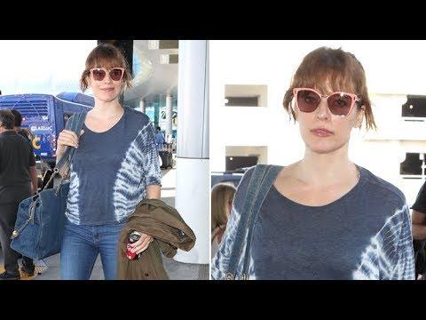 Milla Jovovich Loving Her $5,500 Chanel Denim Tote, Drinking A Classic Coke At LAX