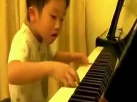 Niño asiático toca magistralmente el piano