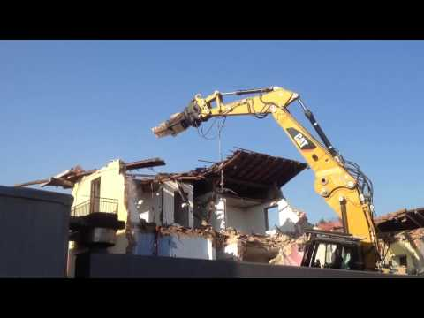 Il dinosauro meccanico mangia il tetto di una casa