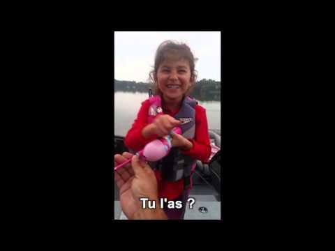Una bambina che pesca un grosso pesce con la sua canna da pesca barbie