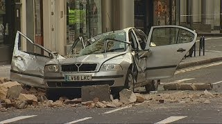 Woman dies after strong winds cause building to fall on car in central London