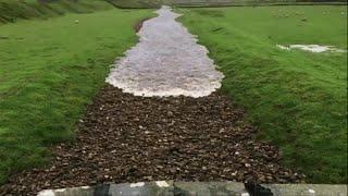 Após fortes chuvas, rio que tinha ressecado na Inglaterra é preenchido por uma corrente d'água.