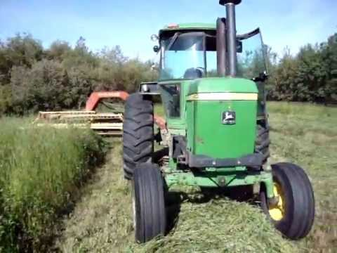 4430 - John Deere 4430 and New Holland 499 hydroswing Haybine mowing hay in the summer of 2011 in the Peace Country of Northern Alberta Canada. Old equipment still ...