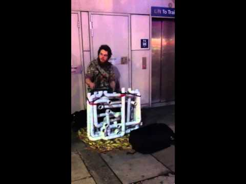 Watch on-THONG busker playing street music using pipes, women's flip flops and underwear