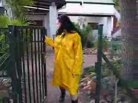 Rainweargirl - Rainweargirl on the farm wearing a yellow PVC rain smock. This smock is the same length as a raincoat and made from slippery PVC with a rubbery feel on the o...