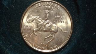 "Delaware State Quarters were released on January 4, 1999 as the first coin in the State Quarter series. Delaware's original Statehood date was December 7, 1787.The reverse design features Caesar Rodney on horseback. The inscriptions include the State name, Statehood date, mintage date, ""E Pluribus Unum,"" ""Caesar Rodney,"" and ""The First State."" The coin's reverse was designed and engraved by William Cousins.Caesar Rodney was a delegate to the Continental Congress. He rode 80 miles on horseback to cast the deciding vote in favor of independence. In his lifetime, he held more public offices than any other Delaware citizen.The final design was selected based on a popular vote from the Delaware's citizens after initial review and approval by the Secretary of the Treasury, Citizens Coinage Advisory Committee, and the Commission of Fine Arts. Two other designs considered but not selected featured a quill pen and parchment and a depiction of Lady Liberty.The Philadelphia mint produced 373,400,000 coins. The Denver mint produced 401,424,000 coins. Proof and Silver proof coins were produced at the San Francisco Mint. The 1999-S Silver Proof Delaware Quarter is generally considered to be the scarcest proof issue to find in top grade of PCGS PR70DCAM or NGC PF 70 Ultra Cameo and commands a significant premium."