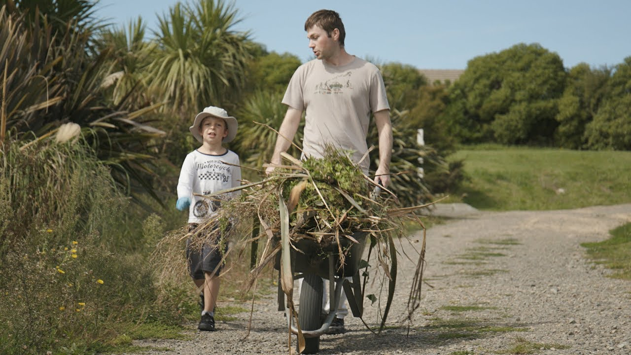 YouTube still shows boy walking alongside man with wheelbarrow filled with weeds.