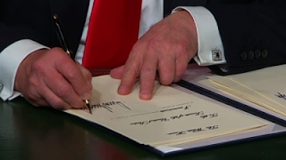 Trump, fond of signing executive orders, awaits more pens