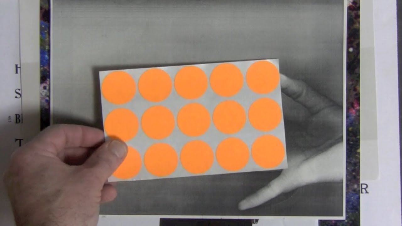 A hand holding a sheet of orange circle stickers over top of photos.
