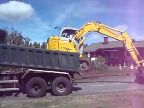 Máy xúc tự leo lên thùng xe tải