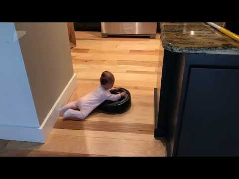Cute Baby Hangs Onto a Roomba to Take a Ride Around the