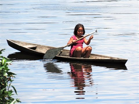 Criança remando canoa em rio do Amazonas