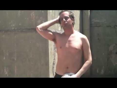 Hombre se saca la remera, sin nada de ropa