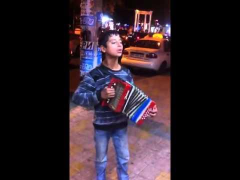Маленький уличный певец на море