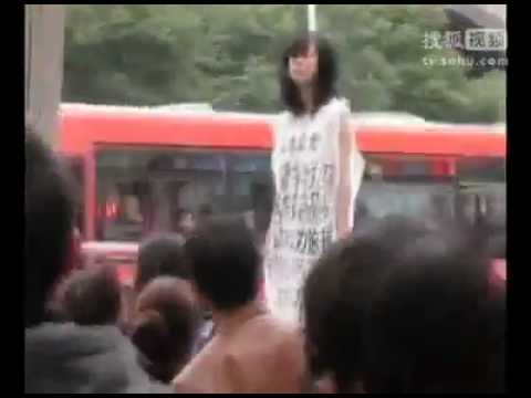 Chinese Nude Model - A Chinese women dressed only with her slogans and standing on a garbage can protested in front of the Supreme Court in Guiyang, China on November 14. 2011. A...
