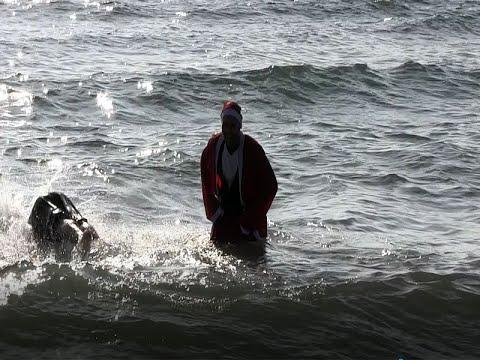 Baño Solidario de Papa Noel, en la Playa Central de Isla Cristina