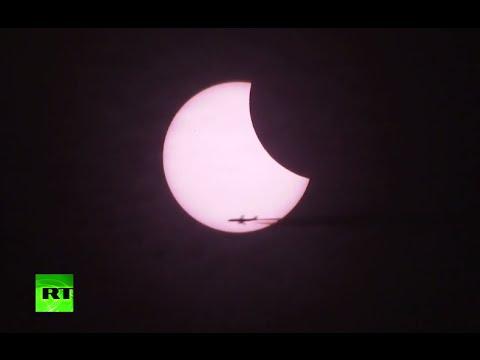 aereo con scia durante l'eclissi solare (russiatoday)