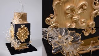 https://www.yenersway.com/tutorials/celebration-cakes/black-and-gold-glam-cakeThis is an introduction and free sample from our Black and Gold Glam Cake tutorial at Yeners Way. The free sample is on how to make Baroque style curly decorations.