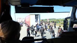 Afrykańscy imigranci szturmujący port Calais widziani z autokaru.