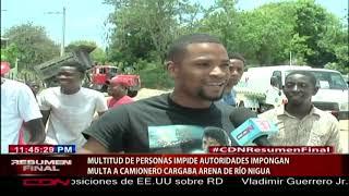 Multitud de personas impide autoridades impongan multa a camionero que cargaba arena de río Nigua