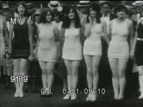 bathing suits women - Footage of 1920s women in bathing suits and swimwear, in various activities: riding on a train locomotive; dancing in a tropical garden; playing with beach b...
