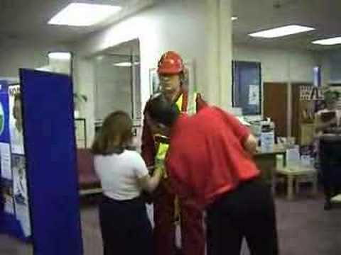 mannequin-man performming as a Living Mannequin: Fall arrest harness being put onto mannequin man by member of the public at a Safety clothing and PPE exhibition by ARCO at family open day at BAE (British Aerospace Engineering) systems in Rochester #1 (flash) for Arco on 06/07/2002