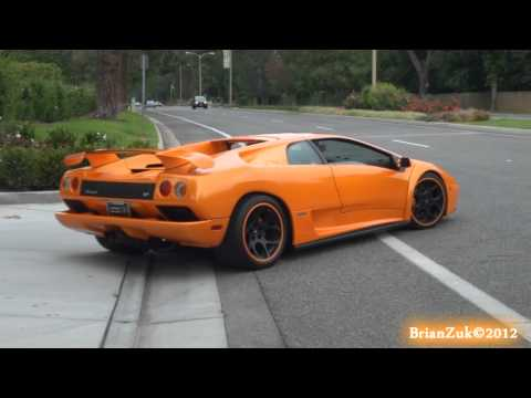 VT - BrianZuk records an insane orange Lamborghini Diablo 6.0 with black wheels with an orange pin stripe, and an aftermarket exhaust accelerating down a street l...