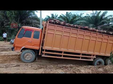 Tuk sawit Truk Tangki CPO dan Dump Truk tarik tarikan di jalan lubang yang ngisap