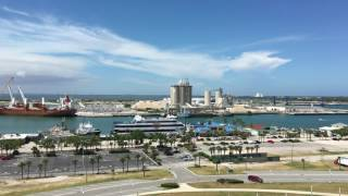 Port Canaveral in Cape Canaveral, Florida and neighboring Cape Canaveral Air Force Station and Kennedy Space Center as seen from the observation deck of the Exploration Tower.  Filmed I 4k Ultra HD July 10th, 2017.The Norwegian Cruise Lines ship Norwegian Gem is at port as well as the Royal Caribbean Majesty of the Seas, the Victory Casino Ship and the Dutch cargo ship Schippersgracht.