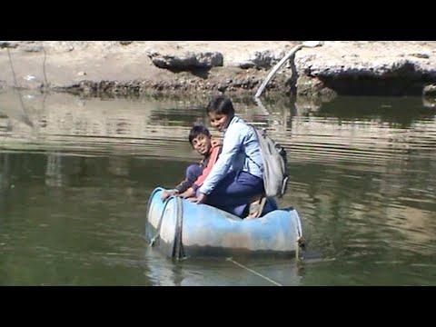 العرب اليوم - شاهد: تلاميذ قرية فقيرة يعبرون النهر بقارب مصنوع من الطبول