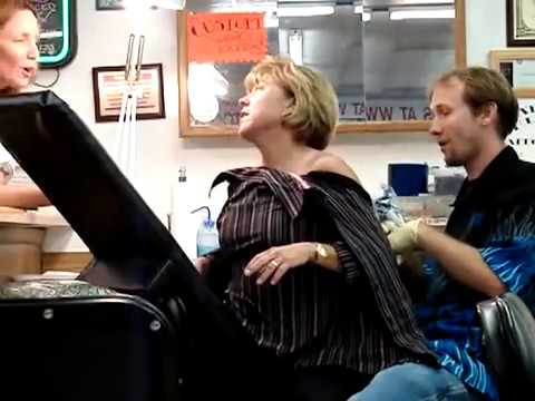 Woman screaming while getting a tattoo (full-length)
