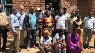 A group of people standing in front of a brick building.