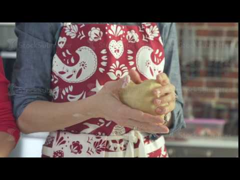Close-up of elastic dough in female hands. Christmas apron