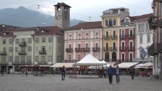 Please subscribe:  http://bit.ly/2pmdyeuSwitzerland playlist  http://bit.ly/2qsUismWe're visiting the town of Locarno, a very pretty little resort town along the shores of Lake Maggiore in southern Switzerland.The old town  has got an extensive arcade – lots of restaurants and ice cream shops, cafés and little stores to poke around in. You can a set have some pizza, pasta, choose from a variety of delicious gelato flavors.The food's Italian, they speak Italian and yet, yes we're in Switzerland.The market sells all kinds of products, especially the local handmade crafted items. There is fabrics and products in wool, ceramics and wooden objects. You can find some wonderful local foods at the market like fresh cheese, eggs, fruits and vegetables, and some of the vendors sell this secondhand merchandise like old CDs and books, and even music tapes and clothing can be found here. It's all very down to earth, very local. These are casual part-time vendors just selling their stuff.We notice the paving and the piazza was smooth water-worn stones in various colors, really quite beautiful.Locarno's old town goes for about six blocks by four blocks so it's not really huge, but it's big enough to enjoy a nice stroll and have a poke around in the art galleries and look in some of the antique stores.Quite a few modern shop-fronts along with the mix.And  we're going to take a little trip over to the nearby village Ascona. Here too, you can go by boat from Locarno, or you can just take the city bus. It only takes about twelve minutes on the city bus to get over here to Ascona.Like Locarno, this town has an Italian feeling to it even though we're still in Switzerland.There really is something very special about this kind of waterfront where you don't have any cars. You've got the lakeside and you've got beautiful buildings with the restaurants and a broad area for pedestrian promenade, and trees and gardens. It seems so classic and typical of your imagination of the ideal waterfront