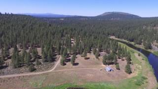 High above the Sprague River in the Modoc-Lassen National Forest by DJI Phantom 3 Standard Drone firmware 1.9.2. It appears to be Mt. Shasta and the Sierra Nevada mountain range in the distance. filmed in the Modoc-Lassen National Forest in Oregon at about 6500 ft above sea level.