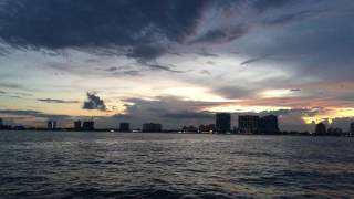 The sun sets over the skyline of Fort Lauderdale, Florida as seen from the deck of a sailboat about a mile off shore in the ocean.