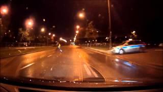 Policjant rzuca latarką w samochód