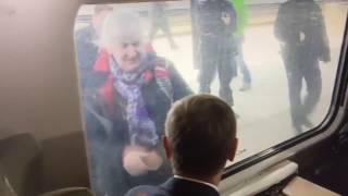Starsza kobieta pozdrawia Donalda Tuska. Przez szybę i na migi :)