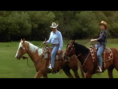 The mother and cowboy ride horses and gallop the prairie