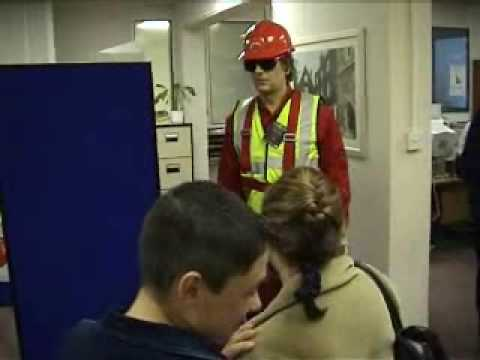 mannequin-man performming as a Living Mannequin: Fall arrest harness being put onto mannequin man by member of the public at a Safety clothing and PPE exhibition by ARCO at family open day at BAE (British Aerospace Engineering) systems in Rochester #8 (flash) for Arco on 06/07/2002