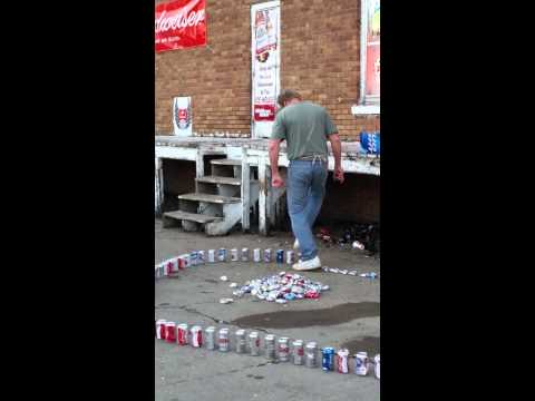 An Agile Man Quickly Crushes a Long Line of Aluminum Cans With His
