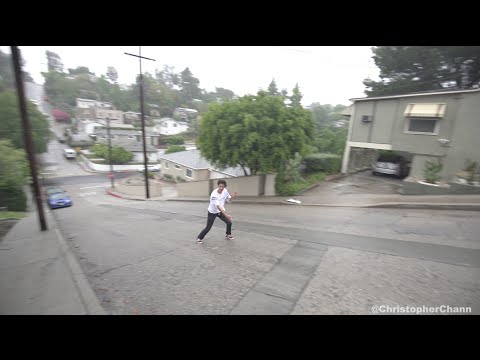 Steep Slide: Skater dudes slide down rainy street with just shoes.