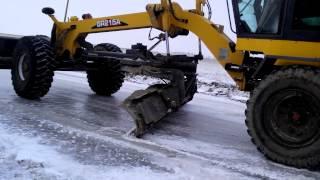 Грейдер GR215 снимает лед с дороги