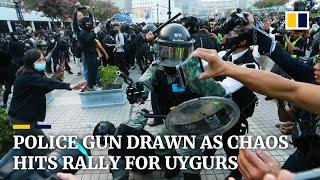 Police gun drawn as Hong Kong rally for China's Uygurs descends into chaos