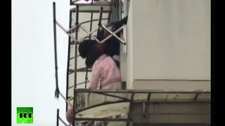 People save toddler trapped on awning in China