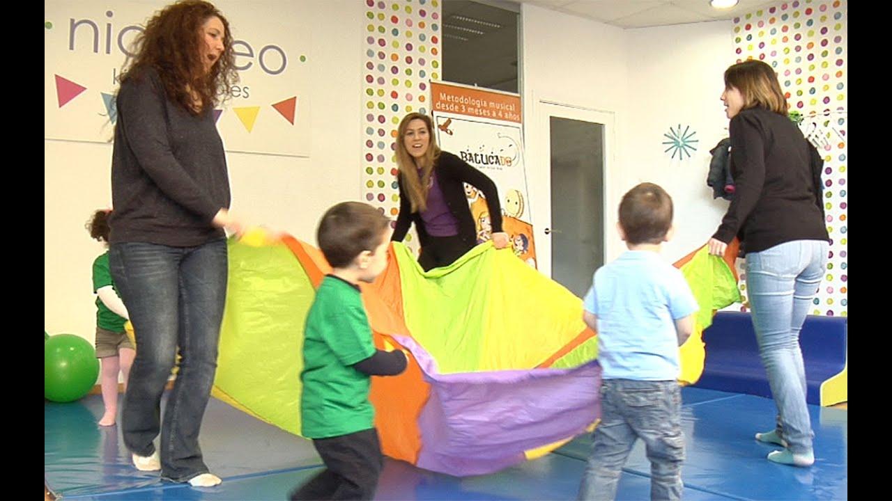 Juego de estimulación psicomotriz para los niños con un paracaídas